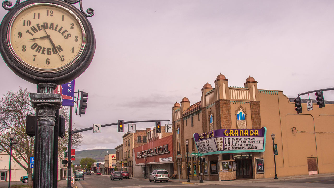A street scene in downtown The Dalles, showing a clock and a movie theater