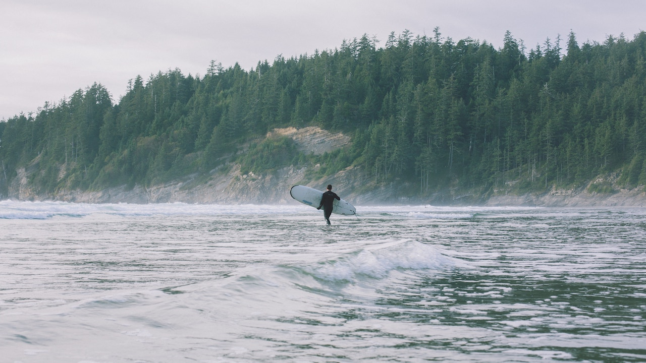 A person holding a surfboard wades into the ocean at a beach in Oregon's Oswald West State Park.