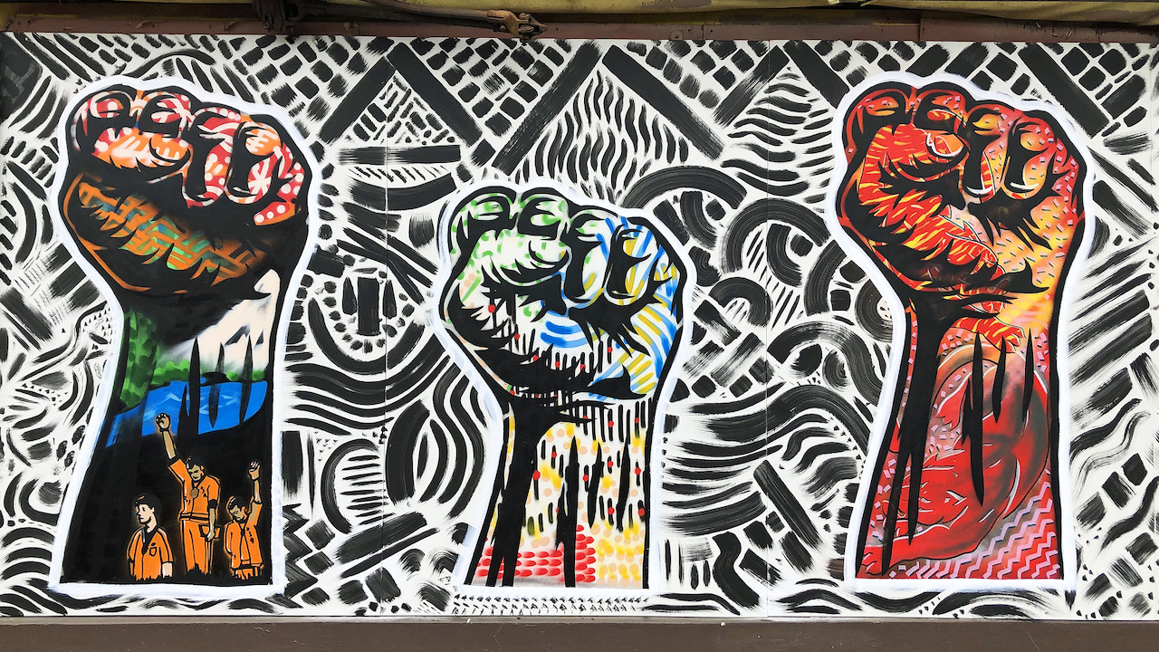 A colorful mural depicting three raised fists.