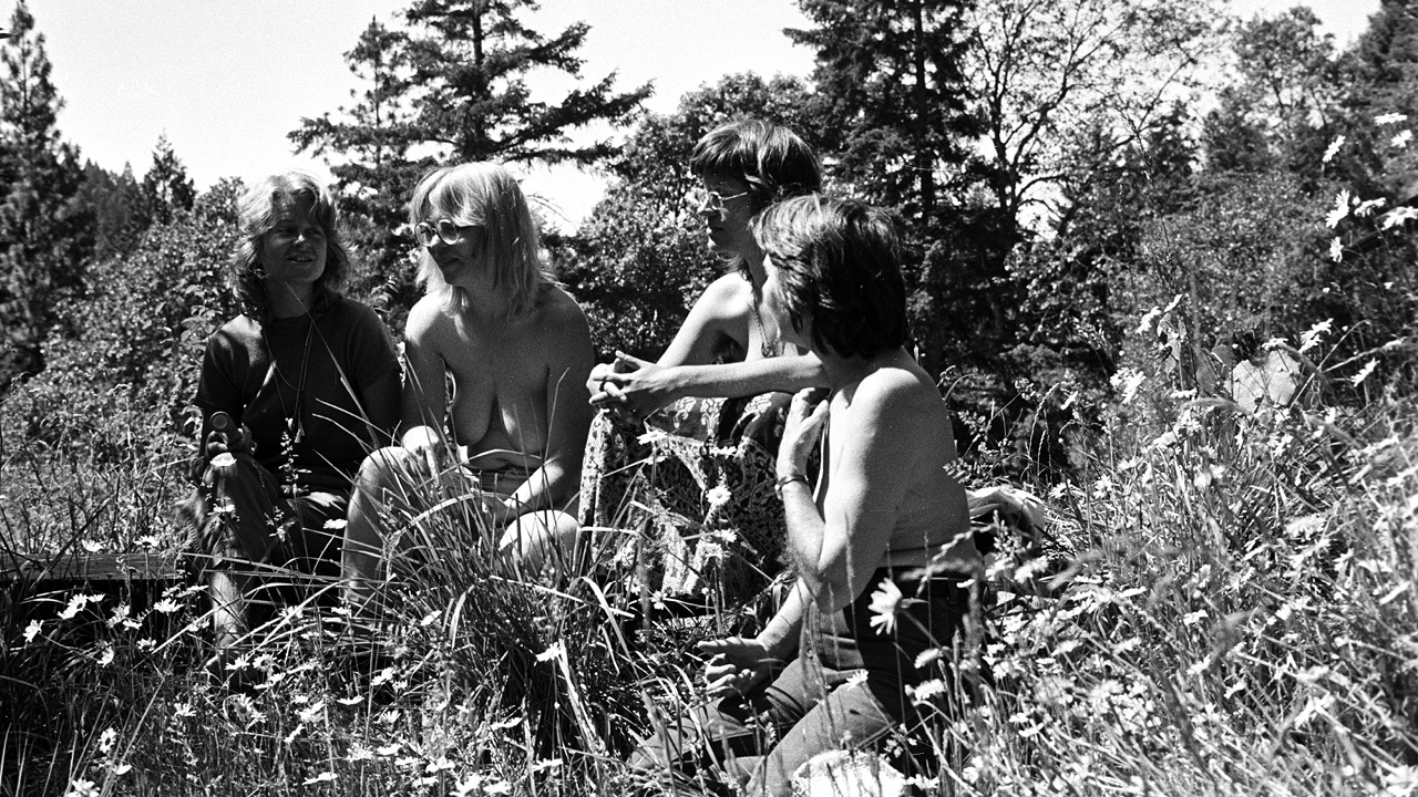 Black and white photograph. Four women, two of them topless, sit on a blanket, conversing, in a field surrounded by fir trees.