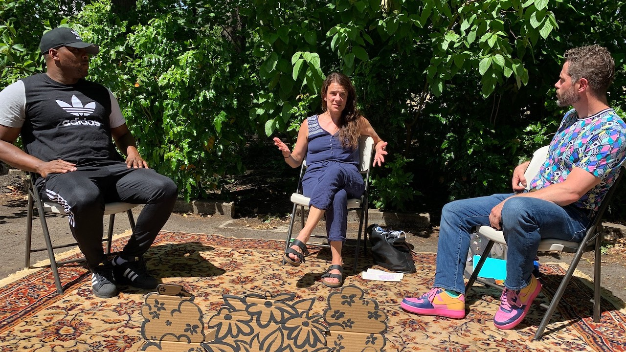Photograph of three people seated outdoors, talking, during the recording of a podcast by City Repair