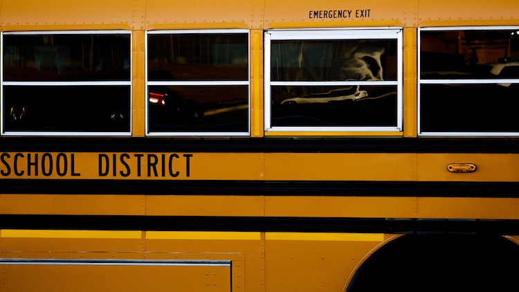 """Yellow school bus with dark, opaque windows reads """"school district"""" and """"emergency exit"""""""