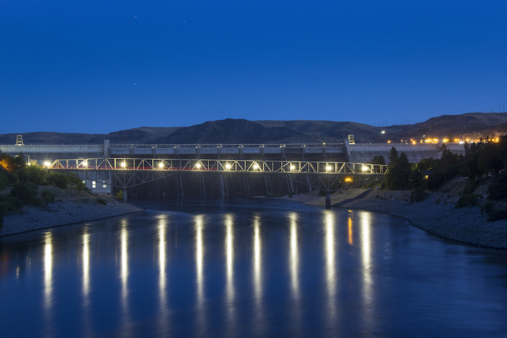 A photo of the Grand Coulee Dam taken at night with lights reflecting off the Columbia River