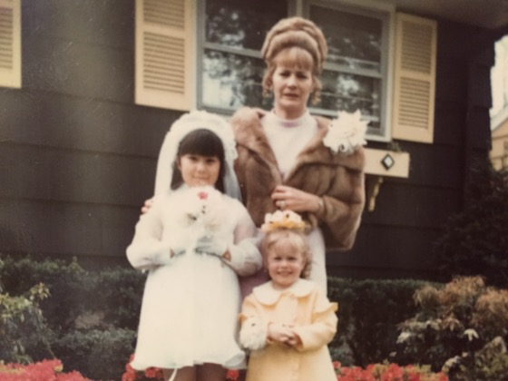 Photo: A dark-haired girl in a first communion outfit holding flowers stands with a woman with blond hair wearing a fur coat and a small girl with blond hair