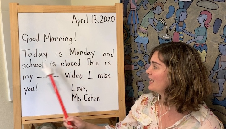 "A woman gestures with a pointer toward a board that reads, ""Good morning! Today is Monday and school is closed. This is my _____ video. I miss you! Love, Ms. Cohen"""