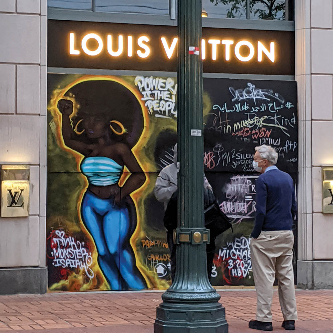 A photo of a street in downtown Portland. The Louis Vuitton store is boarded up, and a mural honoring Breonna Taylor is painted on the boards. An older white man wearing a mask looks at the mural.