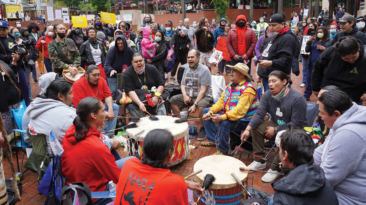 A group of Native American men play drums and sing at a protest at Portland's Pioneer Courthouse Square.