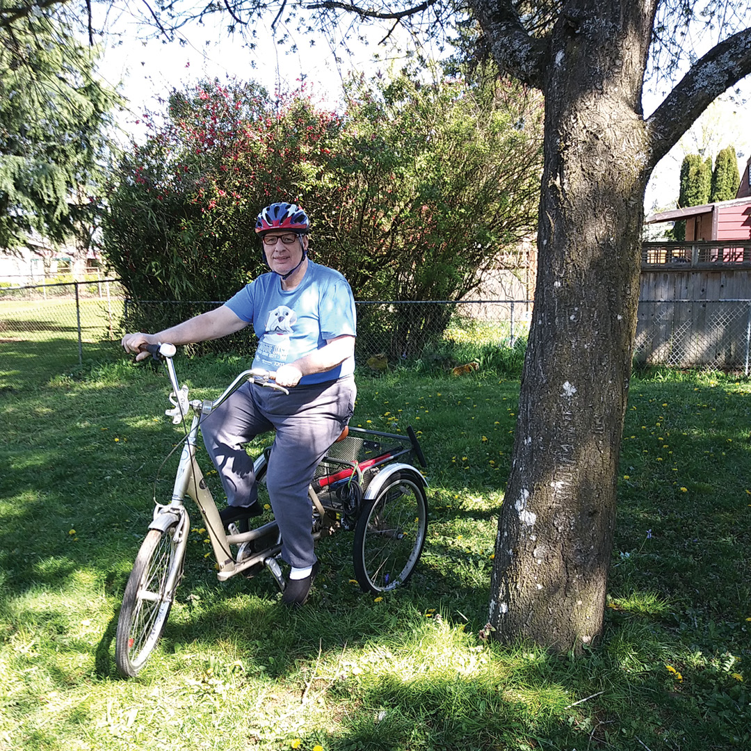 A man rides a three-wheeled bicycle in a back yard