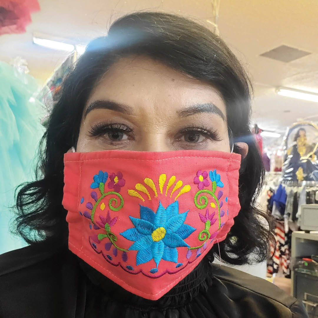 A self-portrait of a woman wearing an elaborately embroidered face mask