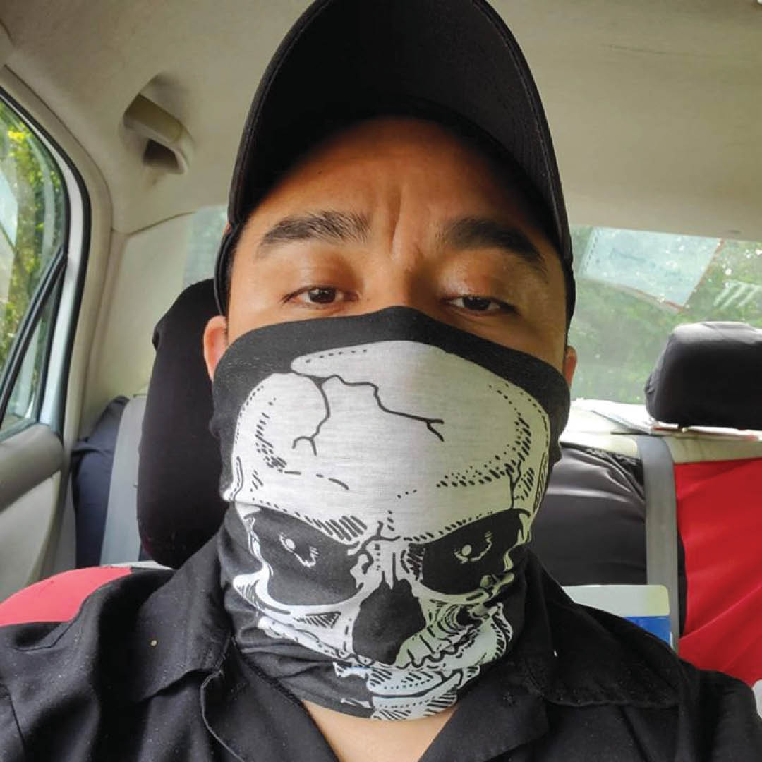 A self-portrait photo of a man wearing a mask and sitting in a car.