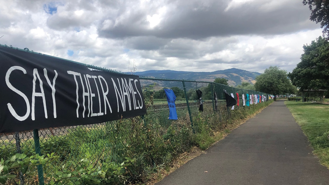 "Before a southern Oregon landscape, a sign reading ""Say Their Names"" hangs on a fence along with T shirts bearing the names of Black men and women murdered by police."