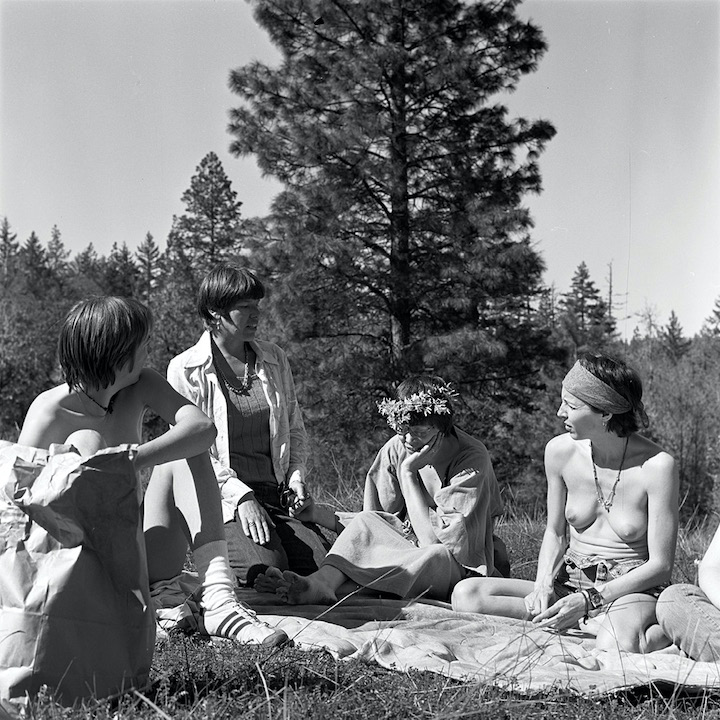 Black and white photo: four women talking outdoors