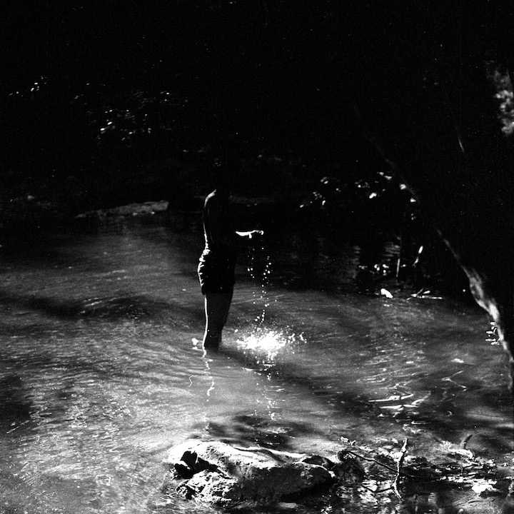 Black and white photo. A woman stands in a creek, water flowing from her cupped hands.