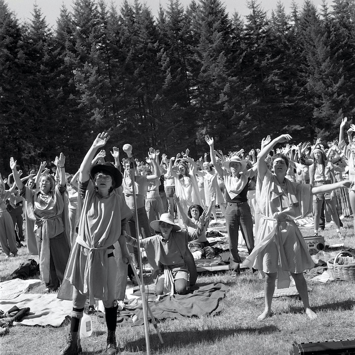 Black and white photo. A crowd of women wave their arms in a clearing surrounded by fir trees.