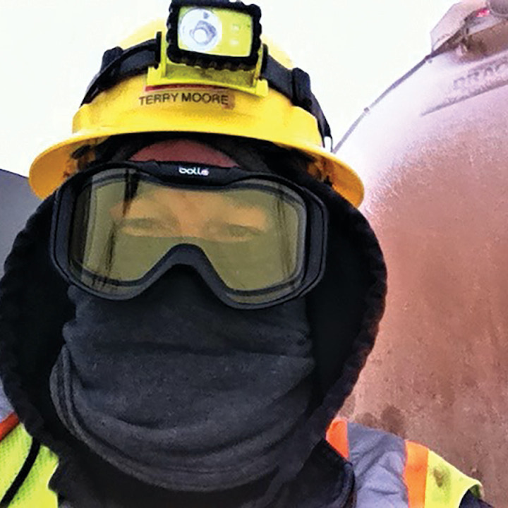 A photo of a man wearing elaborate safety gear, including a helmet, face mask, and eye protection