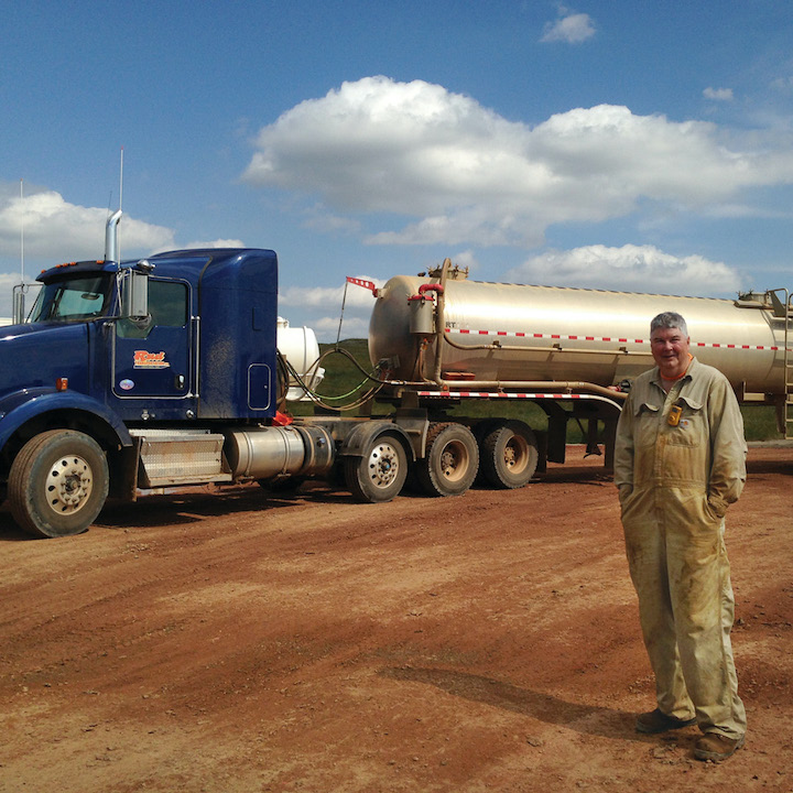 A photograph of a man standing in front of a large tanker truck